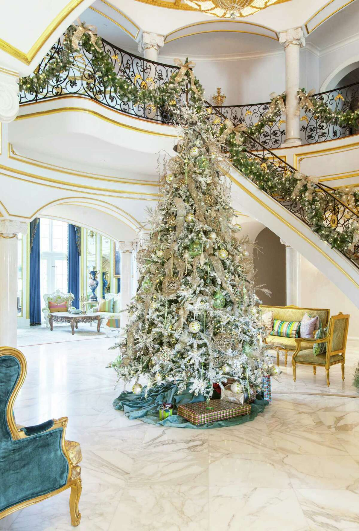 A 12-foot white-flocked Christmas tree fills the first floor of this grand River Oaks home. Designer Regina Gust used approximately 200 oversize ornaments to decorate it.