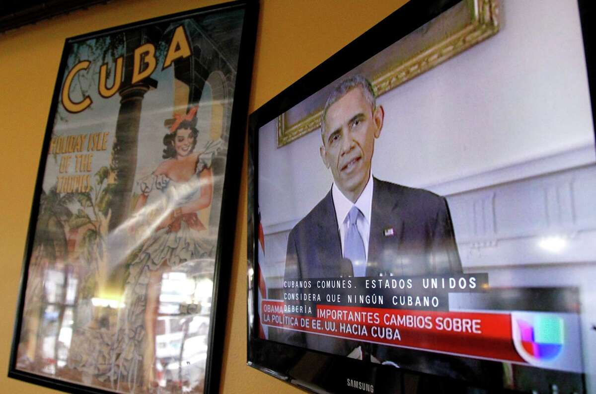 """President Barack Obama is shown on a television screen with Spanish captions as a Spanish language television network shows his speech live inside a Cuban coffee shop, Wednesday, Dec. 17, 2014, in Union City, N.J. Obama announced the re-establishment of diplomatic relations and an easing in economic and travel restrictions on Cuba Wednesday, declaring an end to America's """"outdated approach"""" to the communist island in a historic shift aimed at ending a half-century of Cold War enmity. (AP Photo/Julio Cortez)"""