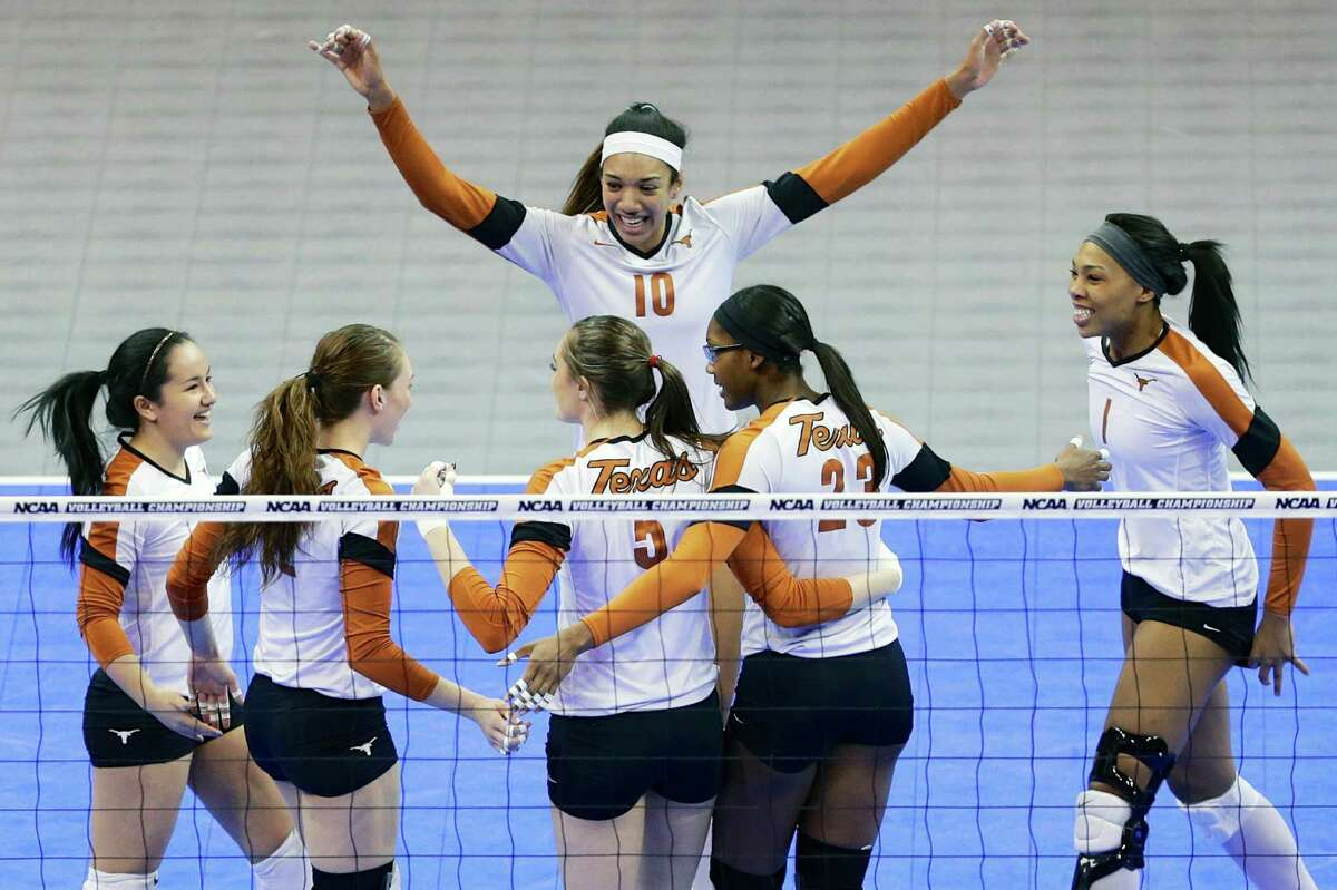 Texas players, including Haley Eckerman (10), Bailey Webster (23) and Khat Bell, right, celebrate a point against American in the semifinals of an NCAA college volleyball regional tournament in Lincoln, Neb., Friday, Dec. 13, 2013.