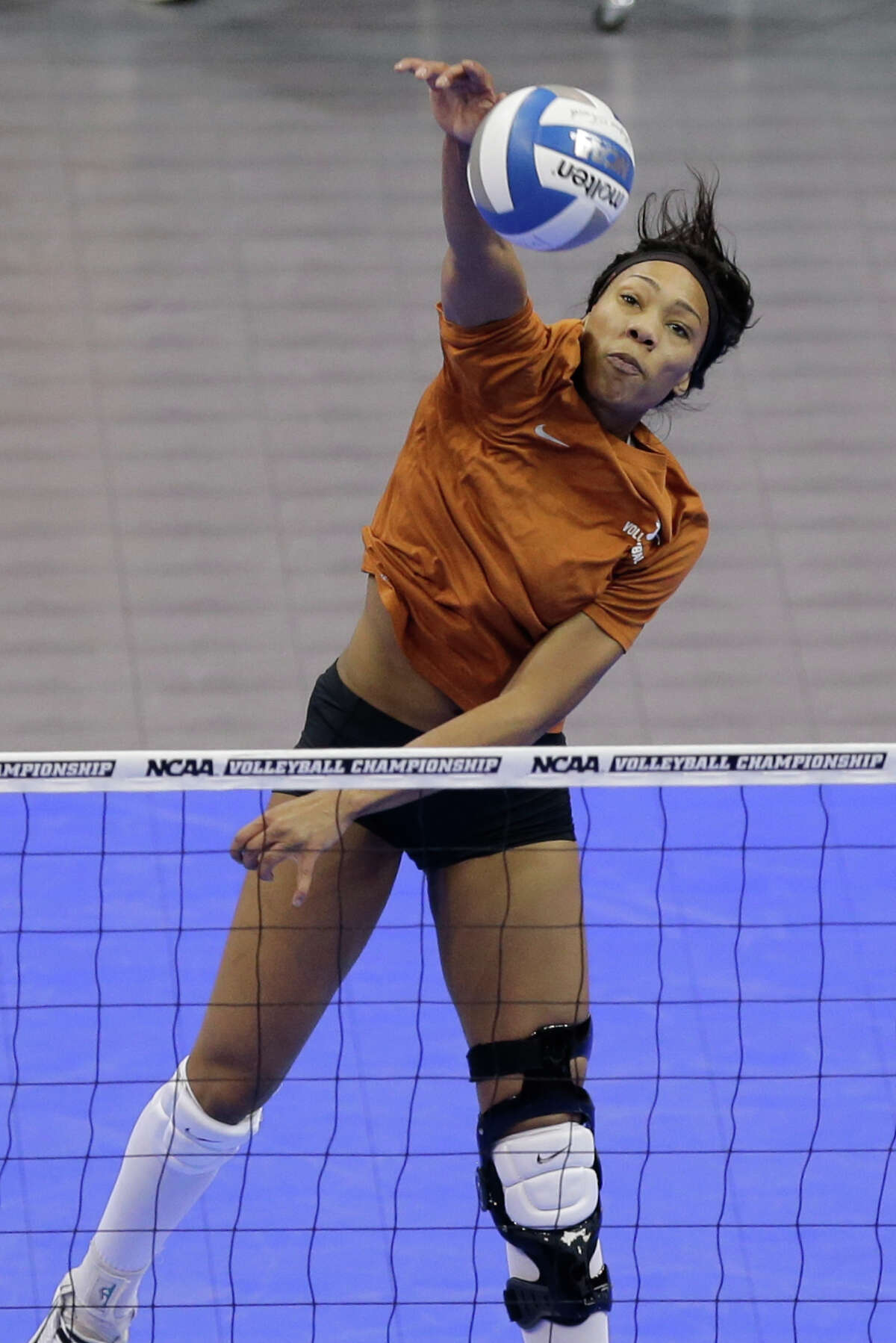 Texas' Khat Bell hits the ball over the net during practice in Lincoln, Neb., Thursday, Dec. 12, 2013. Texas plays American on Friday in the NCAA college volleyball Lincoln regional.