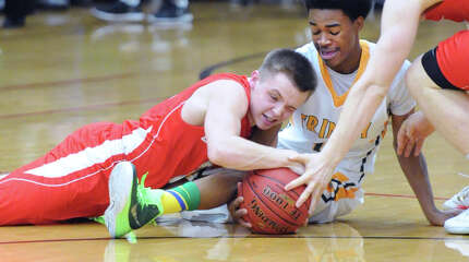 At left, Addison Yost of Greenwich fights for a loose ball with Justice Page of Trinity Catholic during the boys high school basketball game between Trintiy Catholic High School and Greenwich High School at Trinity in Stamford, Conn., Wednesday, Dec. 17, 2014.