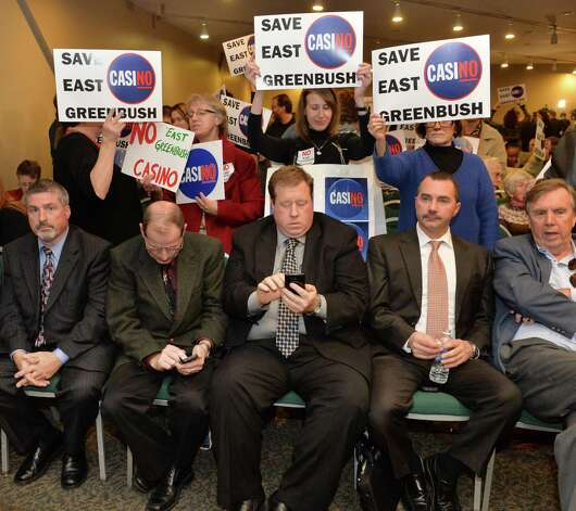 Representatives of the Howes Cavern casino site, bottom, and opponents of the East Greenbush casino site await the New York Gaming Facility Location Board's choices of casino sites during a meeting Wednesday Dec. 17, 2014, in Albany, NY.   (John Carl D'Annibale / Times Union) Photo: John Carl D'Annibale / 00029888A