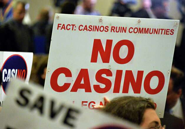 Casino opponents wave signs as they wait for the beginning of the New York Gaming Facility Location Board's  meeting Wednesday Dec. 17, 2014, in Albany, NY.   (John Carl D'Annibale / Times Union) Photo: John Carl D'Annibale / 00029888A