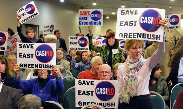 Opponents of an East Greenbush casino wave signs as they wait for the beginning of the New York Gaming Facility Location Board's  meeting Wednesday Dec. 17, 2014, in Albany, NY.   (John Carl D'Annibale / Times Union) Photo: John Carl D'Annibale / 00029888A