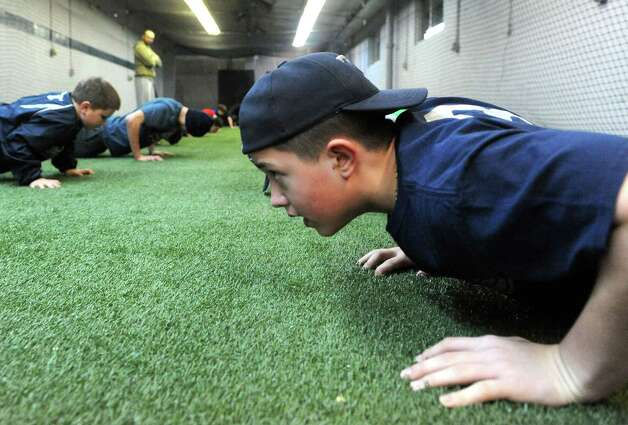Little Bomber eleven-year-old Jason Dessingue does push-ups during Tri City Bombers youth baseball training on Wednesday Dec. 17, 2014 in Troy ,N.Y.  (Michael P. Farrell/Times Union) Photo: Michael P. Farrell / 00029903A