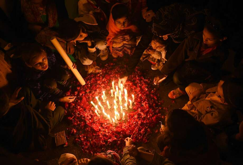 """TOPSHOTS Pakistani children gather around lit candles for the victims of an attack by Taliban gunmen on an army-run school in Peshawar, in Karachi on December 17, 2014. Pakistan army chief General Raheel Sharif and Afghanistan president Ashraf Ghani vowed to fight """"terrorism and extremism"""" together, a day after Taliban militants killed 148 people at a Pakistani school. AFP PHOTO / Asif HASSANASIF HASSAN/AFP/Getty Images Photo: Asif Hassan, AFP/Getty Images"""