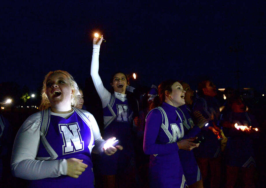 Cheerleaders lead a cheer as the field and stands are alit by flashlights in the big finale of a pep rally Wednesday night at the Newton High School stadium. The Eagles head to Arlington Thursday for their state finals championship game.  Photo taken Wednesday, December 17, 2014  Kim Brent/The Enterprise Photo: Kim Brent / Beaumont Enterprise