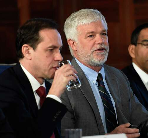 NYS DEC Commissioner Joe Martens, right,  gives his thoughts on fracking as acting Health Commissioner Howard Zucker takes a drink of water during the Governor's cabinet meeting held in the Red Room of the Capital Wednesday afternoon Dec. 17, 2014 in Albany, N.Y.     (Skip Dickstein/Times Union) Photo: SKIP DICKSTEIN / 00029897A