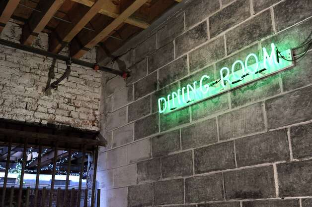 The modern neon sign hangs in sharp contrast to the exposed brick, cinder blocks and wrought-iron gate in the dining area on Wednesday Dec. 17, 2014, at The Tavern in Troy, N.Y. (Cindy Schultz / Times Union) Photo: Cindy Schultz / 00029893A