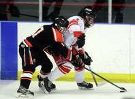 Ridgefield's Alec Knupp and Fairfield Prep's Matt Kernaghan battle for the puck during their match Wednesday, Dec. 17, 2014, at Wonderland of Ice in Bridgeport.
