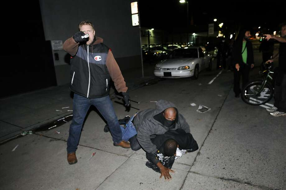 An under cover officer points his gun at the crowd while his partner subdues a protester who struck him in the back of the head, as demonstrations continue for a fifth night in Oakland, CA, on Wednesday, December 10, 2014. Photo: Michael Short, Special To The Chronicle