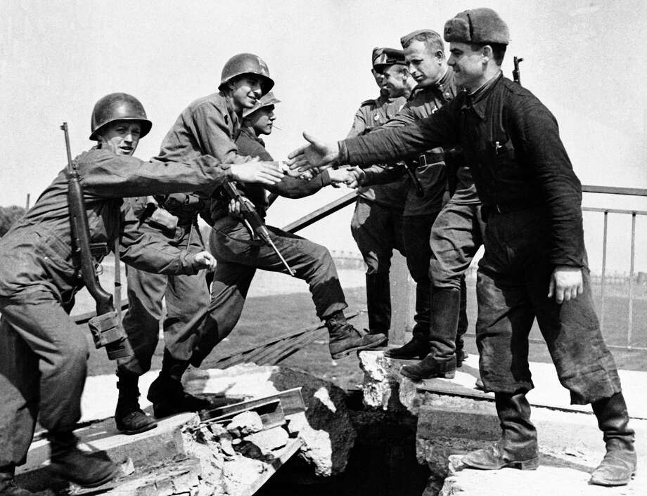 FILE - In this April 26, 1945, file photo, U.S. and Russian troops meet on the wrecked bridge over the Elbe River at Torgau, Germany. The Americans, left, and Russian soldiers are shown as they reach out to grasp each other's hands. The picture is part of an exhibition in Berlin marking the 70th anniversary of the end of World War II. (AP Photo) Photo: Uncredited, STR / Associated Press / AP