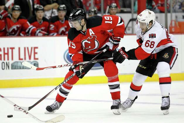 New Jersey Devils center Travis Zajac (19) skates with the puck against Ottawa Senators left wing Mike Hoffman (68) during the second period of an NHL hockey game, Wednesday, Dec. 17, 2014, in Newark, N.J. (AP Photo/Julio Cortez) ORG XMIT: NJJC114 Photo: Julio Cortez / AP