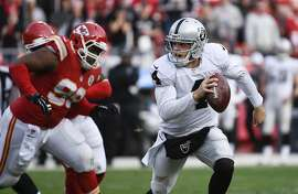 Oakland Raiders quarterback Derek Carr (4) runs from pressure from the Kansas City Chiefs during the second half of their NFL football game in Kansas City, Mo., Sunday, Dec. 14, 2014. (AP Photo/Reed Hoffmann)
