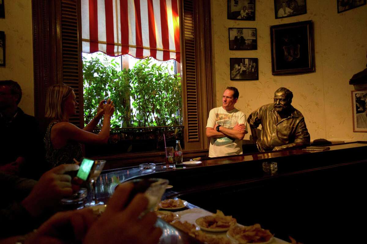 """A tourist is photographed next to an Ernest Hemingway statue at the """"Floridita"""" bar in Havana. Most Americans are banned from traveling to Cuba."""