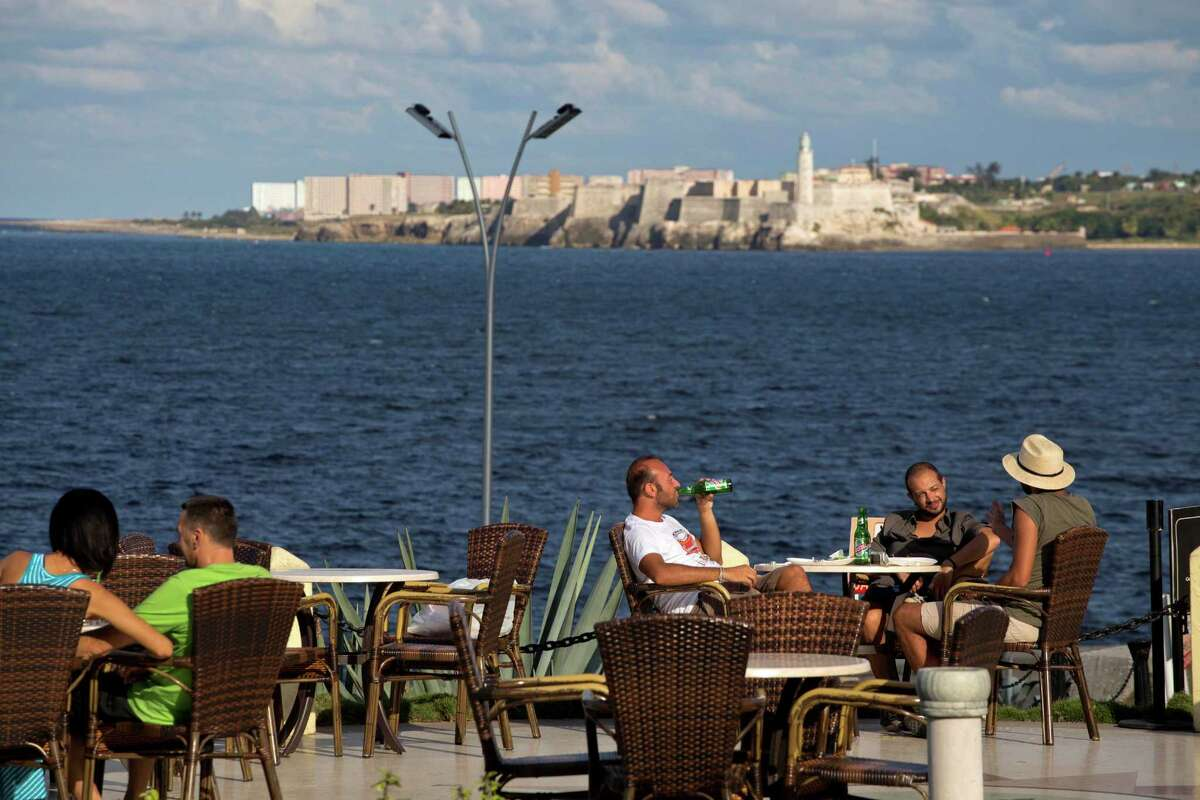 Tourists take a few beers at the Hotel National, with a view of Morro Castle behind them in Havana, Cuba, in this file photo from 2014.