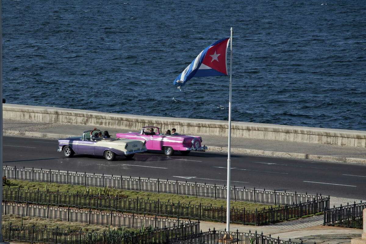 Tourists ride in a classic American car on the Malecon in Havana, Cuba, Wednesday, Dec. 17, 2014. After a half-century of Cold War acrimony, the United States and Cuba abruptly moved on Wednesday to restore diplomatic relations _ a historic shift that could revitalize the flow of money and people across the narrow waters that separate the two nations. The U.S. is easing restrictions on travel to Cuba, including for family visits, official government business and educational activities. But tourist travel remains banned. (AP Photo/Desmond Boylan)
