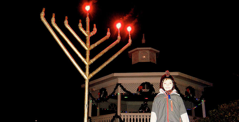Aiden Anderson, 6, of Fairfield, next to a menorah on Sherman Green, where a lighting ceremony Wednesday celebrated Hanukkah, the Festival of Lights. Photo: Mike Lauterborn / Westport News