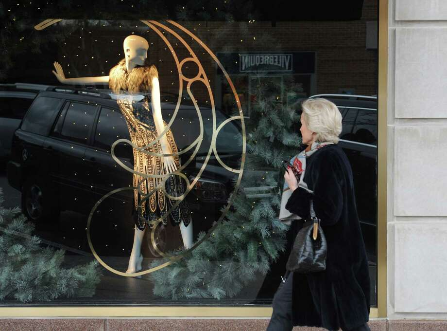 A fur-wearing mannequin in the window of Saks Fifth Avenue exchanges a glance with a woman walking along Greenwich Avenue in downtown Greenwich, Conn. Wednesday, Dec. 17, 2014.  Over the years, many local businesses along the Avenue have been replaced by super high-end stores, changing the look and feel of the downtown area. Photo: Tyler Sizemore / Greenwich Time