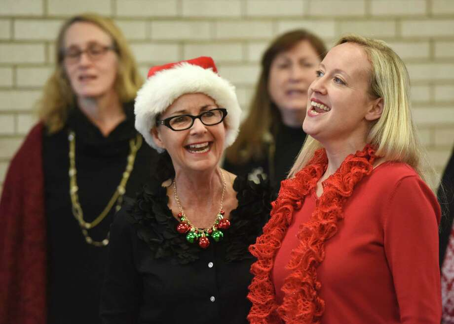 Judy Willsey, left, and Debbie Hires sing Christmas carols with the a cappella group Grace Notes at the Metro-North station in downtown Greenwich, Conn. Thursday, Dec. 18, 2014.  The women's a cappella group entertained folks waiting for the train by singing a variety of holiday songs, an annual tradition for Grace Notes. Photo: Tyler Sizemore / Greenwich Time