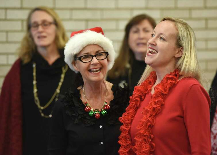 Judy Willsey, left, and Debbie Hires sing Christmas carols with the a cappella group Grace Notes at