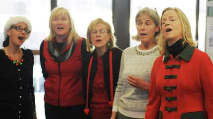 Anne Marcus, right, sings Christmas carols with Grace Notes a cappella group at the Metro-North station in downtown Greenwich, Conn. Thursday, Dec. 18, 2014.  The women's a cappella group entertained folks waiting for the train by singing a variety of holiday songs, an annual tradition for Grace Notes.