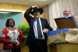 Hardin County Judge Billy Caraway dons a black stetson given as a gift on behalf of Southeast Texas Workforce by Marilyn Smith as county commissioner Ken Pelt looks on during his retirement ceremony Wednesday at the Hardin County Courthouse. Friends, colleagues, officials, and family filled the room, many presenting gifts and sharing their memories of working with Judge Caraway in his 16 years serving on the bench as well as other county positions throughout the years. Judge Caraway will be spending his retirement caring for his beloved longhorn cattle at his ranch home. Photo taken Tuesday, December 16, 2014 Kim Brent/The Enterprise