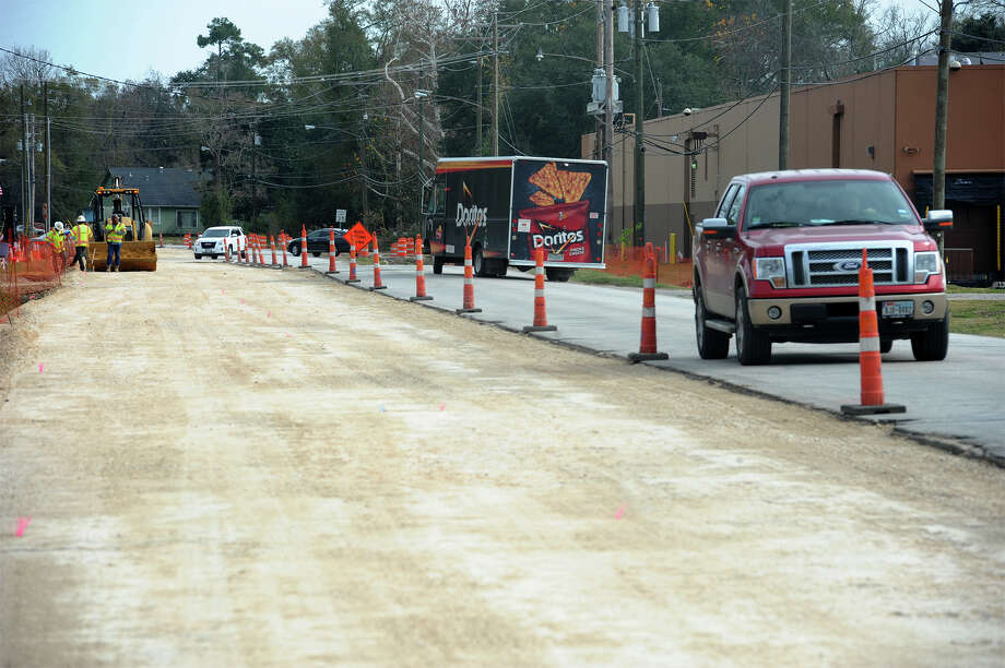 Motorists pass by construction workers on Concord Road Wednesday. The project is about six months behind schedule and is now expected to finish in late 2015.  Photo taken Wednesday, December 17, 2014  Guiseppe Barranco/The Enterprise Photo: Guiseppe Barranco, Photo Editor