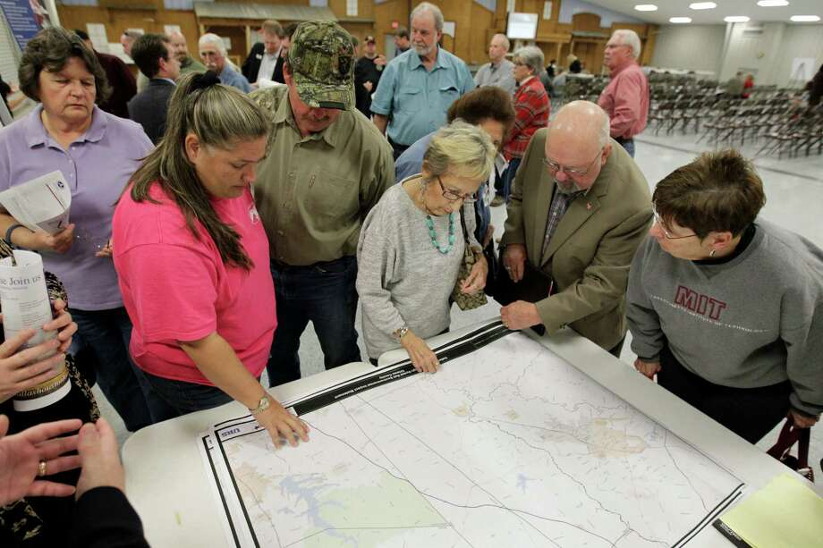 People gather to look at maps as they attend a public meeting on Dec. 4, 2014, in Navasota at the Grimes County Expo Center about the proposed high-speed rail project from Dallas to Houston. The bullet train project has faced intense opposition in rural areas such as Grimes County. Photo: Melissa Phillip, Houston Chronicle / © 2014  Houston Chronicle