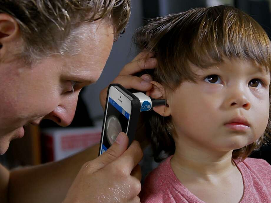 A dad takes video of his son's ear at home.