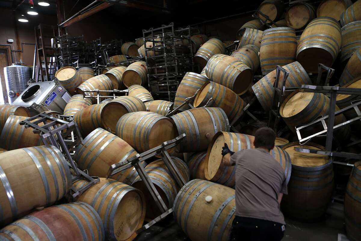 Saintsbury Winery's Ry Richards works on removing the stacks of empty barrels that tumbled over after an earthquake in Napa, Calif. on Sunday, August 24, 2014,