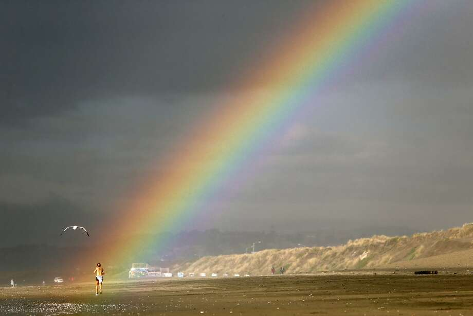 A woman jogs as a rainbow appears over Ocean Beach in San Francisco, Calif., on Monday, December 1, 2014. Photo: Scott Strazzante, The Chronicle