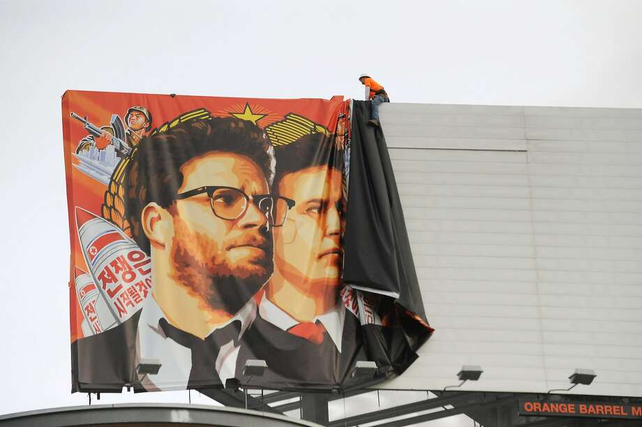 """Workers remove a poster-banner for """"The Interview"""" from a billboard in Hollywood, California, December 18, 2014 a day after Sony announced was cancelling the movie's Christmas release due to a terrorist threat.  Photo: Michael Thurston, AFP/Getty Images"""