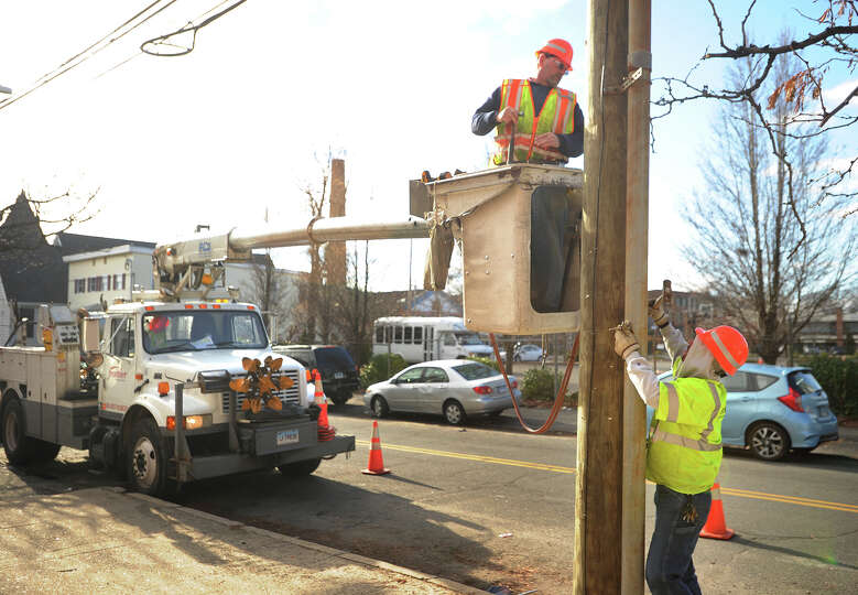 A Frontier Communications crew installs fiber optic cable on Lafayette Street in the South End of Br