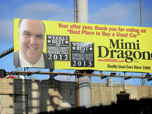 Mimi Dragone' s billboard and close-up shot of owner Camen Dragone still looks down over the recently closed used car business on Fairfield Avenue in Bridgeport, Conn. on Thursday, December 18, 2014. Dragone was arrested by the city's Financial Crimes Unit for allegedly issuing two bad checks.