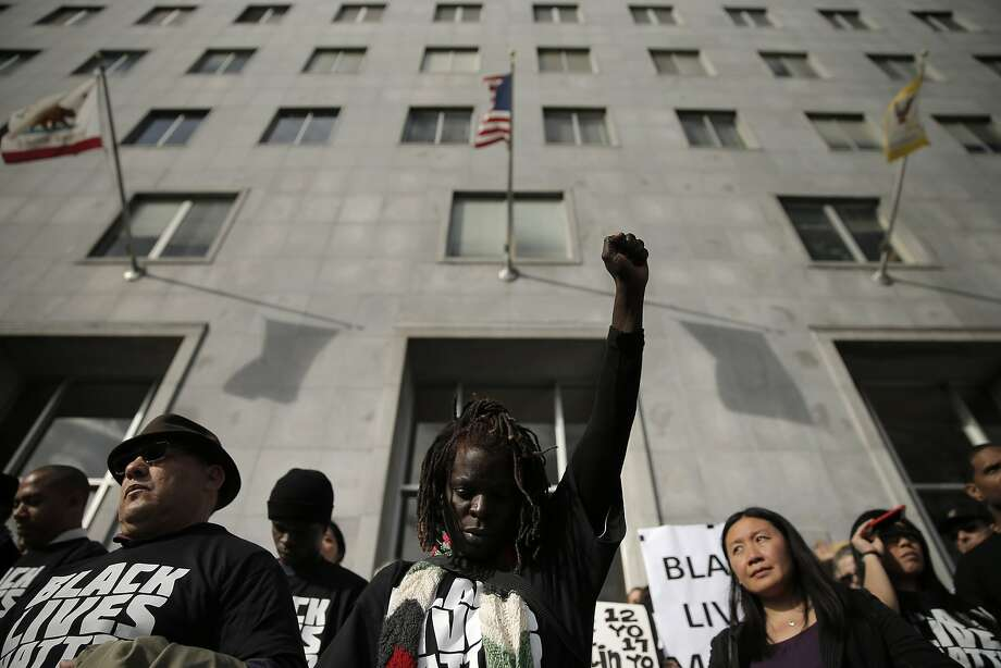 """Charie Pittman of Berkeley holds her fist up on Thursday, during a moment of silence on the steps of the Hall of Justice for Michael Brown and other African Americans killed by police. San Francisco Public Defender Jeff Adachi and several lawyers from his office, along with supportive attorneys, held a """"Hands up, don't shoot"""" protest at the Hall of Justice in San Francisco, Calif., on Thursday, December  18, 2014. The event against police brutality was held in conjunction with similar protests during the day by public defenders in Alameda, Contra Costa and Santa Clara counties. Photo: Carlos Avila Gonzalez, The Chronicle"""