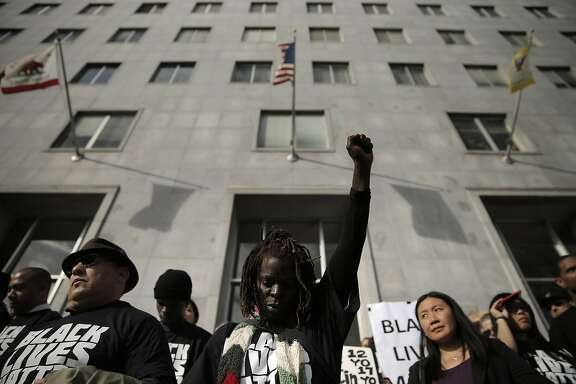 "Charie Pittman of Berkeley holds her fist up on Thursday, during a moment of silence on the steps of the Hall of Justice for Michael Brown and other African Americans killed by police. San Francisco Public Defender Jeff Adachi and several lawyers from his office, along with supportive attorneys, held a ""Hands up, don't shoot"" protest at the Hall of Justice in San Francisco, Calif., on Thursday, December  18, 2014. The event against police brutality was held in conjunction with similar protests during the day by public defenders in Alameda, Contra Costa and Santa Clara counties."
