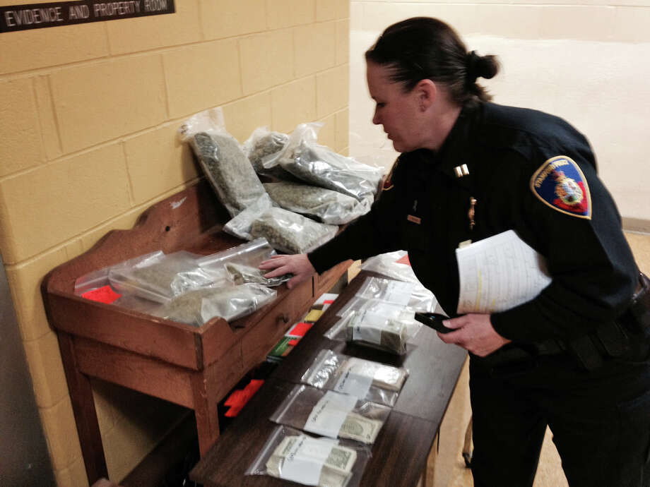 Police Capt. Beth Erickson looking at more than five pounds of marijuana and $9,000 seized by patrol officers following a traffic stop on Stamford's West Side Wednesday afternoon. Photo: John Nickerson / Stamford Advocate