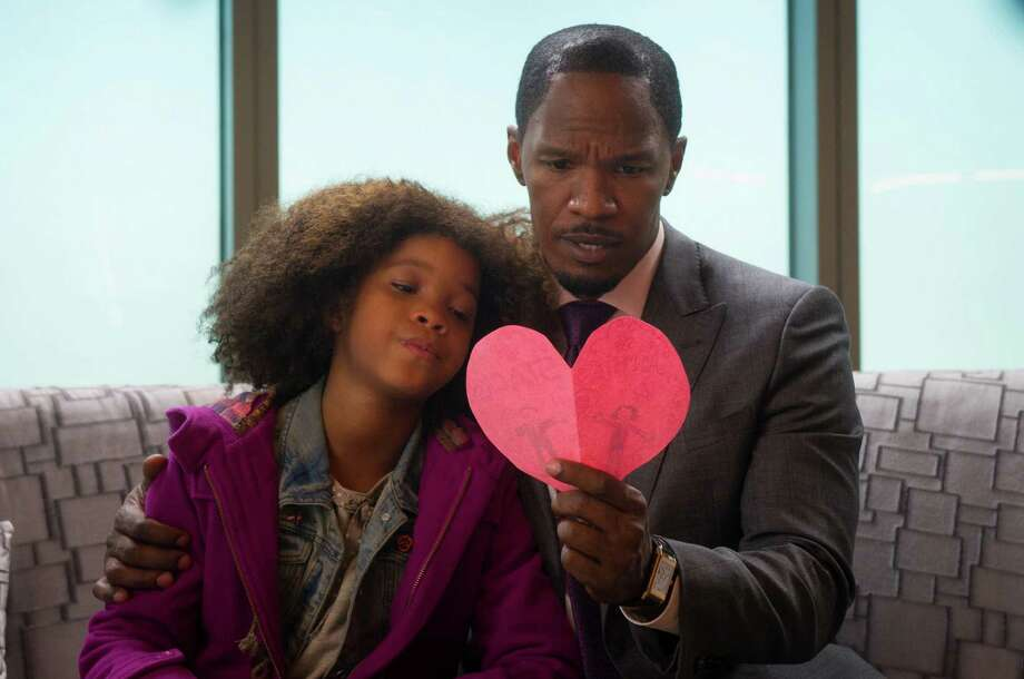 """This photo released by Colombia Pictures - Sony shows Quvenzhane Wallis, left, as Annie, and Jamie Foxx as Will Stacks, looking at a card she made for Stacks in a scene from Columbia Pictures' """"Annie."""" (AP Photo/Columbia Pictures - Sony, Barry Wetcher) ORG XMIT: CAET104 Photo: Barry Wetcher / Columbia Pictures - Sony"""
