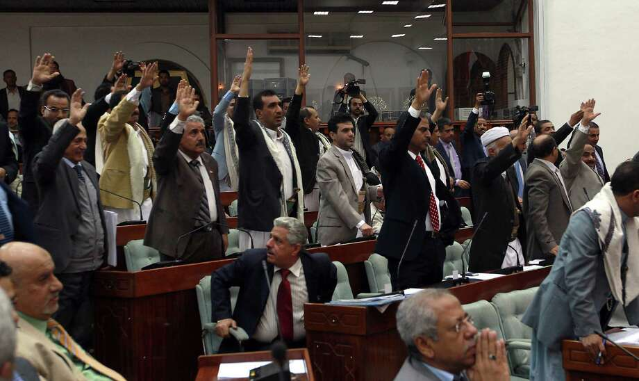 Yemeni Parliament members raise their hands to vote on the policies of the newly appointed government during a session of parliament in Sanaa on December 18, 2014. The new government of Prime Ministr Khaled Bahah won a confidence vote in Yemen's House of Representatives with a comfortable majority following months of unrest.  AFP PHOTO/ MOHAMMED HUWAISMOHAMMED HUWAIS/AFP/Getty Images Photo: MOHAMMED HUWAIS / AFP/Getty Images / AFP