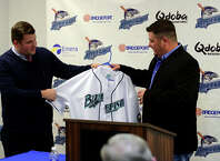 The Bluefish baseball team's new manager Ricky VanAsselberg, at right, is given his game jersey by General Manager Jamie Toole, during a press conference at the Ballpark at Harbor Yard in Bridgeport, Conn. on Thursday Dec. 18, 2014.