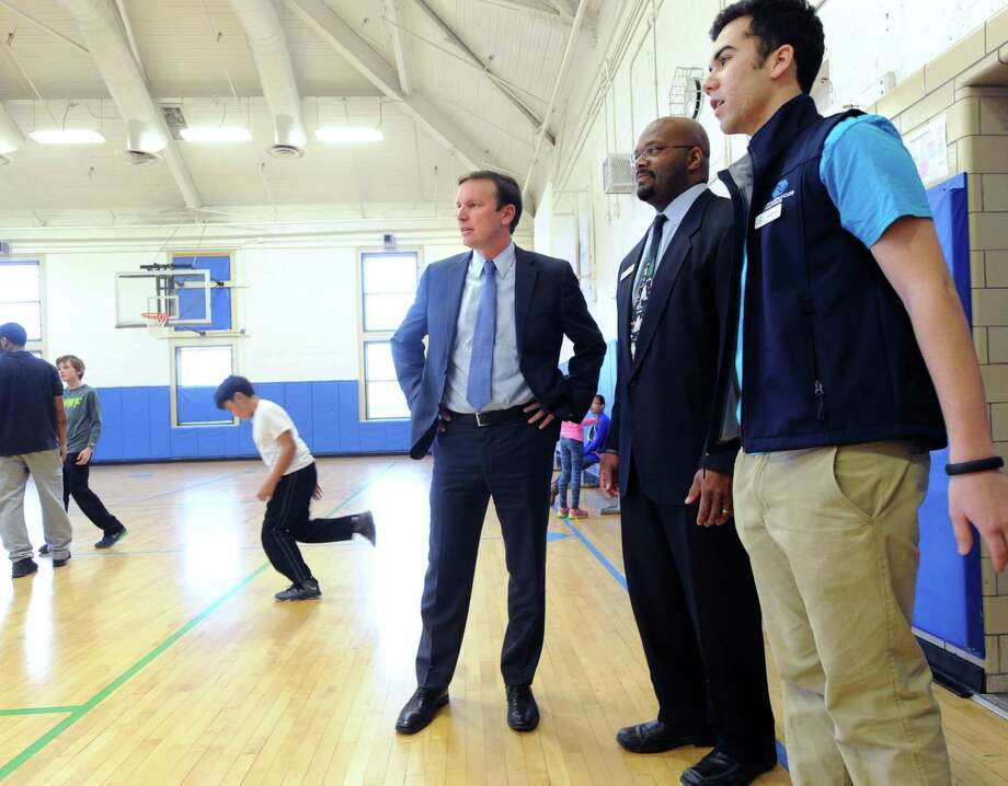 Boys & Girls Club of Greenwich Youth of The Year award winner, Matheus Chaves, 18, right, a Greenwich High School senior, and Bobby Walker, Jr., chief executive officer of the Boys & Girls Club of Greenwich, center, give a tour of the club to  U.S. Sen. Chris Murphy, D-Conn., left, at the club in Greenwich, Conn., Thursday, Dec. 18, 2014. Photo: Bob Luckey / Greenwich Time