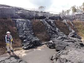 A USGS Hawaiian Volcano Observatory worker stands next to hardened lava at the former Pāhoa transfer station, which has now become the public viewing area to witness the effects of the ongoing  June 27th lava flow.
