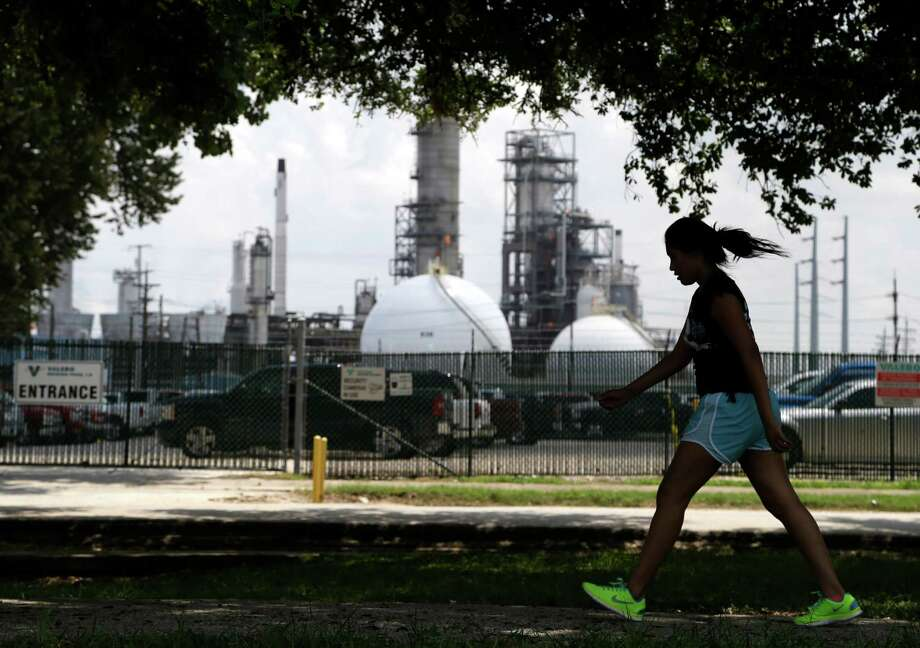 A teenage girl walks around the track of a park across the street from the Valero refinery in the Manchester neighborhood of Houston. A divided Houston City Council approved a deal to consider the refinery to be outside city boundaries for tax purposes. Photo: Associated Press File Photo / AP