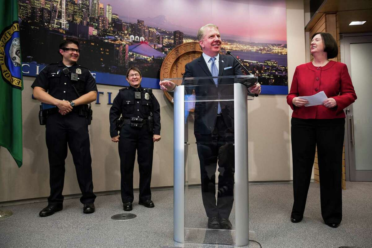 Mayor Ed Murray, center, and Seattle Police Chief Kathleen O'Toole, right, discuss the launch of the Seattle Police Department's new body-worn camera pilot project and accompanying new uniforms Thursday, Dec. 18, 2014, at City Hall in downtown Seattle, Washington.