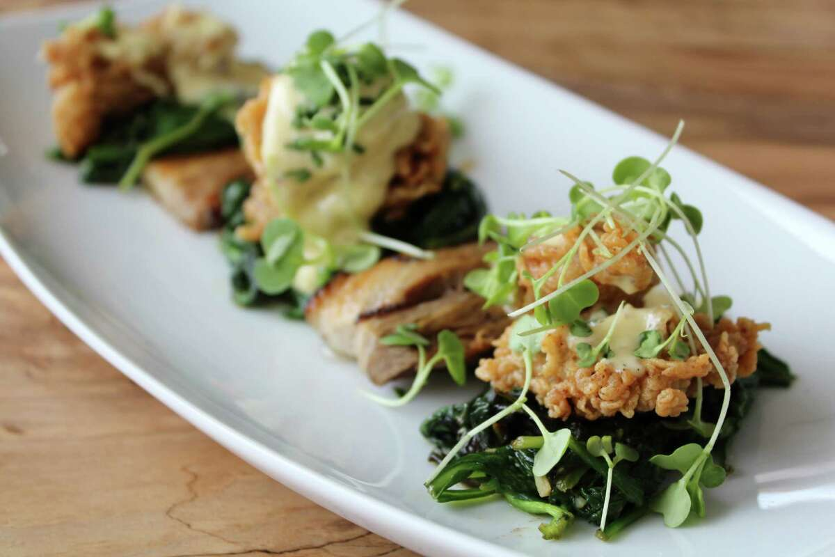 At Silo Terrace Oyster Bar, signature chicken fried oysters on the small plates menu are served with sauteed spinach, braised pork nelly, tart apples and mustard hollandaise.