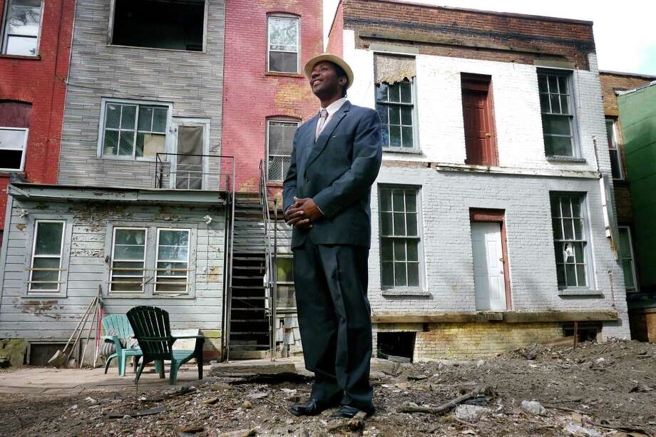 Mark Robinson stands in the backyard of apartment buildings he owns on Lexington Avenue and First Street on Thursday, July 25, 2013 in Albany, NY.  Robinson has along with family members have rehabbed or are in the process of rehabbing the buildings. (Paul Buckowski / Times Union) Photo: Paul Buckowski / 00023298A