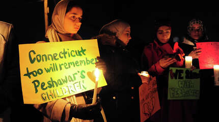Amina Seyal, of Fairfield, holds a sign as she takes part in a candle light vigil to honor and remember the victims of Tuesday's school massacre in Pakistan, at Seaside Park in Bridgeport, Conn. on Thursday Dec. 18, 2014.