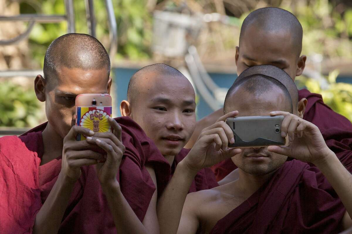 Buddhist monk take pictures at a court house as they await to see New Zealand citizen Philip Blackwood after a court hearing in Yangon, Myanmar, Thursday, Dec. 18, 2014. Blackwood, general manager of the V Gastro Bar, and two Myanmar business partners have pleaded innocent to charges they insulted religion by posting an advertisement with an image of a pink Buddha wearing headphones. (AP Photo/Gemunu Amarasinghe)