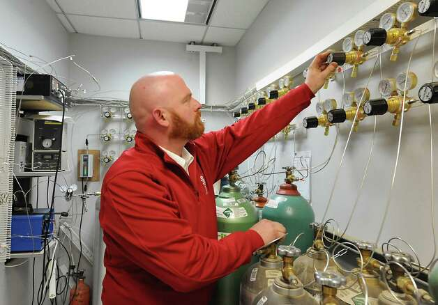 Lab Manager Marty Hogan adjusts a two stage regulator which controls the flow of gases from the cylinders to the gas chromatograph for analysis in the new lab at Noble Gas Solutions on Thursday Dec. 18, 2014 in Albany, N.Y. Noble Gas Solutions provides gases to the nanotech sector among other companies and corporations.  (Lori Van Buren / Times Union) Photo: Lori Van Buren / 00029917A